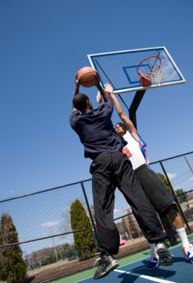 Photo of two students playing basketball.