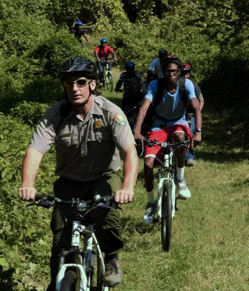 A National Park Service ranger leads an adventurous group on a bike ride through DC's Fort Dupont Park.