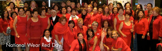 A group of mostly women dressed in red dresses, red shirt, red sweaters sit and stand as they pose for the camera in celebration of National Wear Red Day.