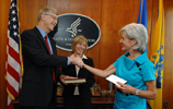 NIH Director Francis Collins and HHS Secretary Kathleen Sebelius shaking hands after he is sworn in with his wife, Diane Baker, looking on