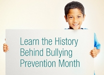 Boy holds sign on history of bullying prevention month.