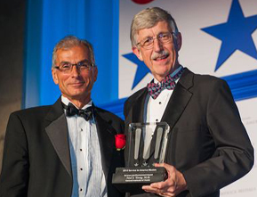 Dr. Young and Dr. Collins holding a glass award on a stage