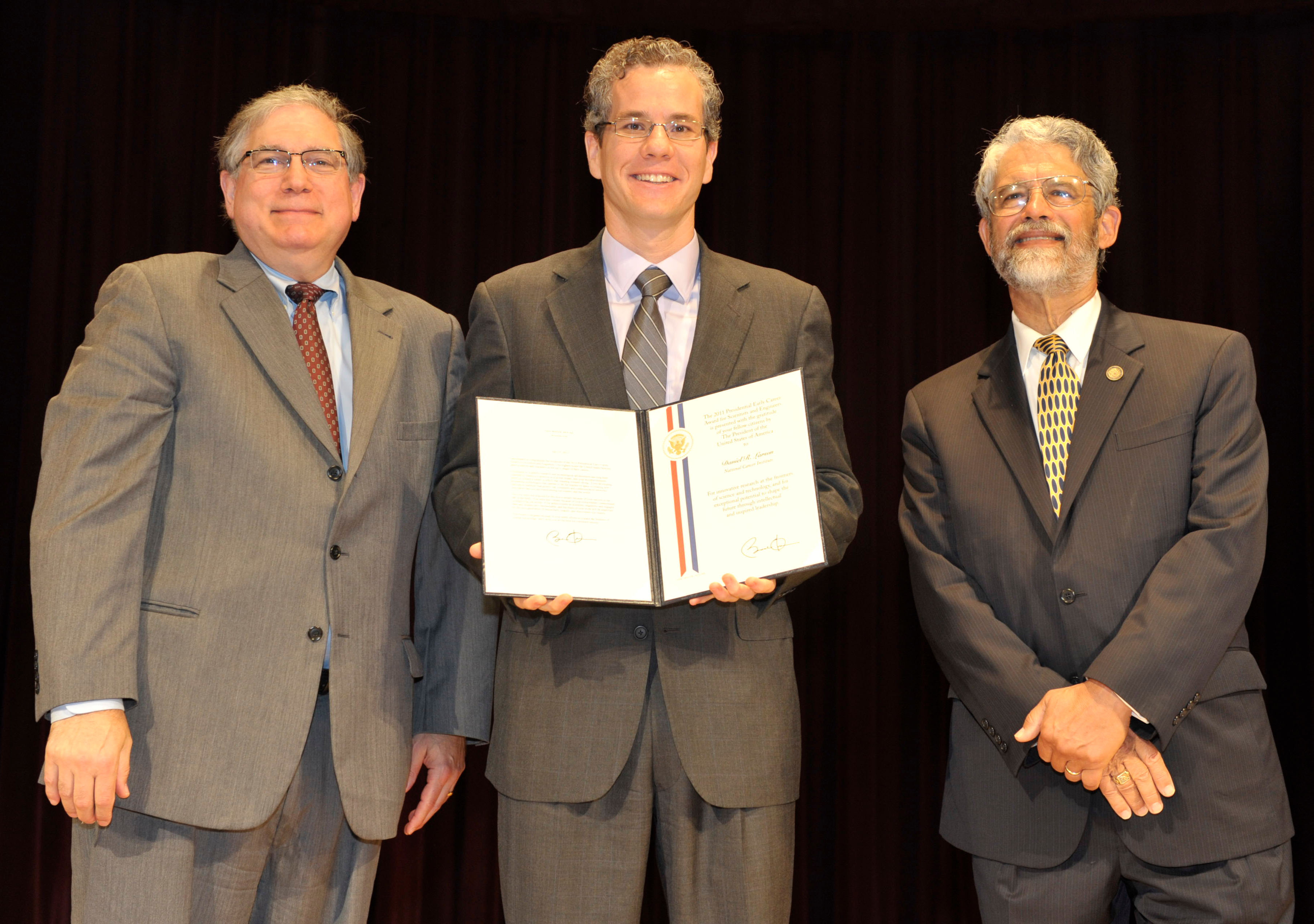 Dr. Larson stands between Dr. Tabak (left) and Dr. Holdren (right), while holding his award