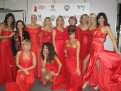 11 Argentinean celebrity women wearing designer red dresses posing after the Argentinean Red Dress Collection Fashion Show. Two women are kneeling and the rest are standing behind them. The image also includes Dr. Cristina Rabadan-Deihl