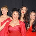9 celebrity women from The Heart Truth's 2007 Fashion Show wearing designer red dresses pose together backstage after the show.