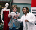 An older woman is checking her BMI as a health care professional in a white Dr.'s coat assists her. Both women are standing in front of a mannequin that is wearing a formal red dress.