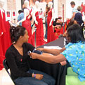 One young woman in a black v-neck shirt is having her blood pressure checked by a health care professional as she sits in front of a display of formal red dresses on mannequins.