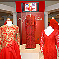 5 mannequins wearing First Ladies red dresses on display on a white dais.