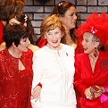 Mrs. Laura Bush in a white skirt suite with a Red Dress Pin in between Liza Minnelli and Rita Moreno who are both in red outfits, posing at the end of the 2008 fashion show.