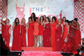 17 celebrity women from The Heart Truth's 2010 Fashion Show wearing designer red dresses laughing and waving to the audience at end of the 2010 fashion show. They are standing in front of a large The Heart Truth Red Dress logo.