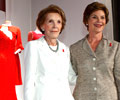 Mrs. Nancy Reagan in a white skirt suite and Mrs. Laura Bush in a gray skirt suit with a Red Dress Pin pose in front of several First Ladies red dresses.