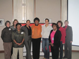Nine women from the 2009 Buffalo Champions stand in front of a Heart Truth display.