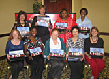 In Canton, Ohio, 9 women pose holding their speaker kits from a Champions training class.