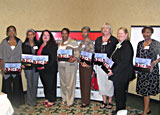 8 women in Sacramento, California, in a Champions training class, stand holding their speaker kits.