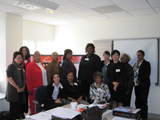 Thirteen women from the Baltimore Champions pose together in front of a Heart Truth display.