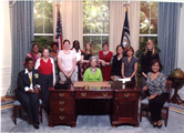 Thirteen women in College Station, Texas, gather in a room resembling the Presidential Oval Office.