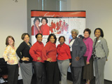 Eight women pose in front of the Memphis Champions Heart Truth display.