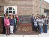 Thirteen female champions from Louisville stand outside of the Presbyterian Community Center.