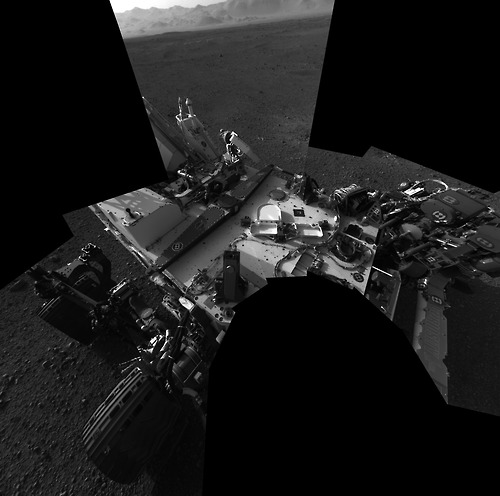 Image description: I, Robot. This self-portrait by the NASA Curiosity rover on the surface of Mars is a mosaic made up of 8 images taken on August 8. Curiosity is using these first days after landing to check its systems. The back of the rover can be seen at the top left of the image, and two of the rover's right side wheels can be seen on the left. Part of the pointy rim of Gale Crater forms the lighter color strip in the background. Bits of gravel, about 0.4 inches (1 centimeter) in size, are visible on the deck of the rover.