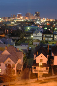 Photo of a cityscape, starting with suburban homes in front and extending out to a full city skyline.