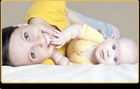Una mujer y su bebé sonríen, ambos  vistiendo camisetas amarillas,