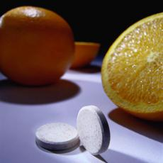 Photograph of oranges and vitamin C supplements