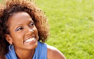Una mujer con camiseta azul y aretes largos sonríe mientras mira al horizonte