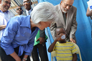 HHS Secretary Sebelius mixes and provides oral rehydration for a child with cholera at the GHESKIO center in Port-au-Prince, Haiti. With Dr. Bill Pape (left), Director of GHESKIO. Credit: Photo by Jean Jacques Augustin.