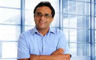 Un hombre con camisa azul mira de frente cruzado de brazos