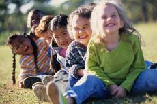Fotografía de niños sonrientes sentados afuera