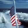 American flag at the back of a boat at sea.