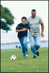 A boy plays soccer with an adult male