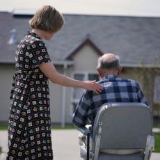Fotografía de una cuidadora asistiendo a un hombre mayor en un silla de ruedas