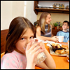 A girl drinking a glass of milk, with her family in the background
