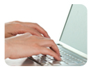 Image of hands typing on a laptop