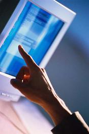 Fotografía de una mano señalando la pantalla de una computadora