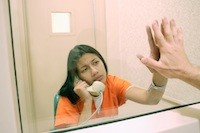 Woman in prison on phone behind glass