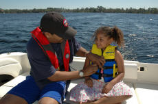 Photograph of a father and daughter on a boat, both wearing life jackets