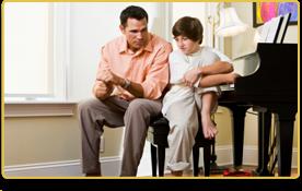 Un niño y su padre hablan sentados junto al piano