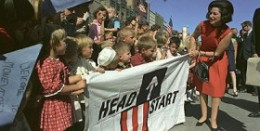 Photo of teacher and kids holding a Head Start banner