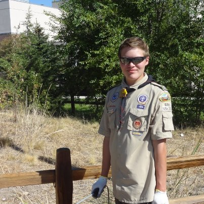 """Photo: Monument Fence Gets Boost from Boy Scouts  On a warm, sunny Saturday day in September, the split-rail fence at the National Firefighters' Monument got a badly needed boost. About 20 people affiliated with Boy Scout Troop #315 turned out to support Michael Schone fulfill one of the final requirements needed to obtain the rank of Eagle. Each Eagle Scout candidate must develop, organize, oversee and complete a project that benefits the community before receiving the honor.  Michael's project came in two stages: First, prep the fence by pressure-washing one week, and then staining it the next. Gaining approval for a suitable project by the Boy Scouts of America (BSA) organization was one of the more difficult chores for Michael. The BSA has strict standards for Eagle Scout project proposals and Michael approached several community organizations, none of which had a suitable project for him.  """"Just finding a project was a challenge,"""" he says. """"We got turned down a lot.""""  He learned of the need through a circuitous route. First came Michael's dental hygienist, Brian Halle, who was aware of the need for an Eagle project. Next came one of the dentist's patients, Tim Murphy, BLM assistant director at NIFC. That led to a call from Tim Murphy to Einar Norton, NIFC's supervisory engineer.  The discussion in the dentist's chair was the catalyst for Michael getting in touch with Einar. After that, the dots connected quickly.   Behind every Eagle Scout is usually a determined mother. That was certainly the case for Michael. """"It feels wonderful to finally complete this journey toward the Eagle; I'm very proud of him,"""" says Noel Schone, who modestly described her role as, """"Keeping him focused and reminding him.  I'd call it 'gentle persuasion.'""""  The project was a family affair. Along with his mother, Michael's father, Ryan, brother Steven (also an Eagle Scout) sister Heather, uncles, cousins and grandparents all supported him.    Overall, he estimates about 95 hours of work """