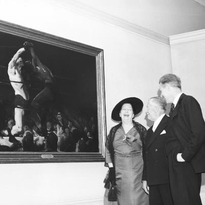 """Photo: In 1957, the art of George Bellows was the subject of the Gallery's first retrospective exhibition focused on the work of a single artist.  """"A Retrospective of the Work of George Bellows"""" (January 19–February 24, 1957) was installed in the West Building Ground Floor Central Gallery and in adjacent rooms, where most temporary exhibitions were shown at the time. The Gallery had undertaken the exhibition with the encouragement of the great collector and Gallery trustee Chester Dale, who had been Bellows' friend and patron. In 1945, exactly 20 years after the artist's death, Dale presented the Gallery with the first works by the artist to enter the collection, including """"Both Members of this Club"""" (1909). Don't miss this boxing masterpiece in """"George Bellows,"""" currently on view in the West Building through October 8!  Image: Mrs. George Bellows, Chester Dale, and Gallery Director John Walker with """"Both Members of this Club"""" at the exhibition opening preview, January 19, 1957. National Gallery of Art, Washington, D.C., Gallery Archives"""
