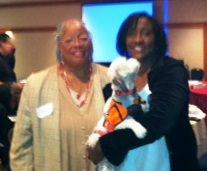 "Photo: Rev. Angela Lundy and Rosalind McKelvey (holding Rev. Lundy's assist dog, Iris) at the Second Annual Functional Needs Symposium on October 2, 2012. The theme of the event was, ""Emergency Communication: Are You Speaking the Right Language?"" and the focus was on emergency communications for people with sensory disabilities."