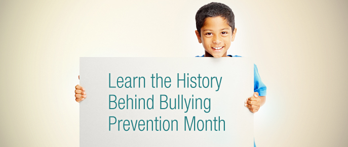Boy holds sign on history of bullying prevention month