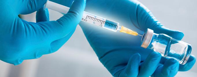 gloved hands holding a syringe
