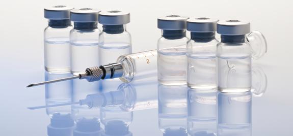 Six vials of medicine and a syringe