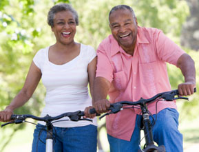 Photograph of an older couple riding bikes outside.