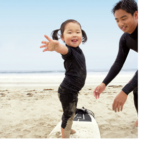 a dad teaching surfing to his daughter
