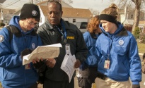 Members of FEMA Corps and a FEMA Community Relations (CR) specialist review a street map while doing reaching out to residents in Union Beach, N.J.