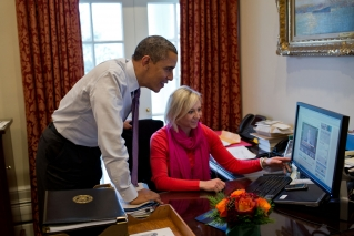 President Barack Obama and Personal Secretary Anita Decker watch a video of David Axelrod shaving off his mustache, in the Outer Oval Office, Dec. 7, 2012. (Official White House Photo by Pete Souza)